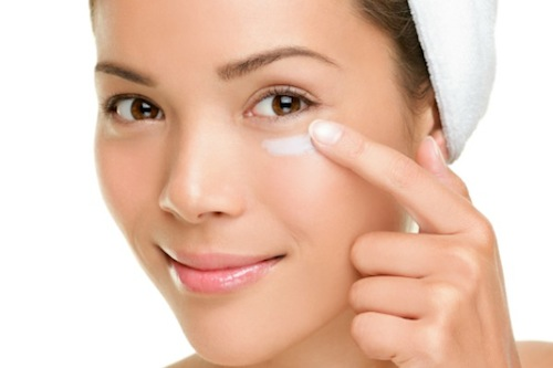 Skin care woman putting face cream
